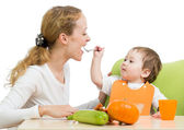 Playful baby spoon feeding his mother isolated on white — Stock Photo