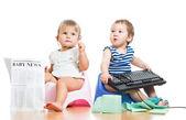 Roliga barn flicka och en pojke som sitter på chamberpot med tidningen — Stockfoto