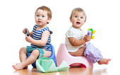 Babies toddlers sitting on chamber pot and playing with toys — Foto Stock