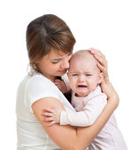 Mother trying to comfort her crying baby isolated — Stock Photo