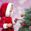 Pretty child decorating Christmas tree on bright background — Stock fotografie