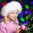 Pretty preschool girl decorating Christmas tree over bright fest — 图库照片