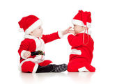 Two funny small kids in Santa Claus clothes isolated on white ba — ストック写真