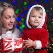 Baby girl and her mother holding giftbox on bright festive backg — ストック写真