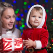Baby girl and her mother holding giftbox on bright festive backg — Foto de Stock
