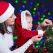 Child girl with mother decorating Christmas tree on bright backg — Stock Photo #13716687