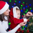 Child girl with mother decorating Christmas tree on bright backg — Stock Photo