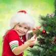Pretty preschool girl decorating Christmas tree on green background — Stock fotografie
