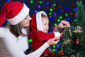 Child girl with mother decorating Christmas tree on bright backg — Stockfoto