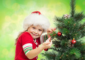Pretty preschool girl decorating Christmas tree on green background — Stock Photo