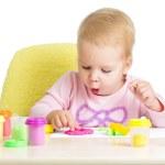 petit enfant assis à table, jouant avec de l'argile coloré — Photo