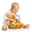 Adorable child with clothes of doctor and teddy bear over white — Stock Photo #13860443