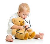 αξιολάτρευτο παιδί με ρούχα του ιατρού και αρκουδάκι πάνω από λευκό — Φωτογραφία Αρχείου