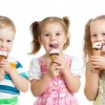 Happy children boy and girls eating ice cream in studio isolated — ストック写真 #14019485