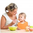Mother spoon-feeding her baby girl — Stock Photo