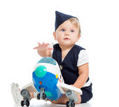 Baby girl dressed as stewardess with airplane toy — Stock Photo