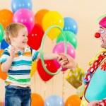 Clown amusing kid boy on birthday party — Stock Photo