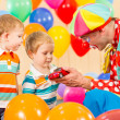 Stock Photo: Clown making present child boy on birthday party