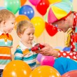 Clown making present child boy on birthday party — Stock Photo