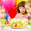 Kids celebrating birthday party and blowing candles on cake — ストック写真