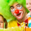 Kids with clown celebrating birthday party and blowing candles o — Stock Photo
