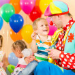 Stock Photo: Happy children and clown on birthday party