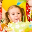 Kids celebrating birthday party and blowing candles on cake — Stock Photo #14139608