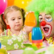 Child girl playing with clown on birthday party — Stock Photo