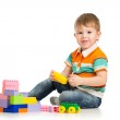 Cheerful child boy playing with construction set over white back — Stock Photo #14139618