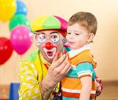 Joyful kid with clown on birthday party — Stock Photo