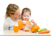 Young mother spoon feeding her baby boy isolated on white — Stock Photo