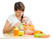 Young mother spoon feeding her baby girlisolated on white — Stock Photo