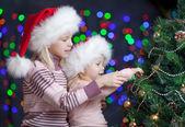 Dětí sestry v santa claus klobouky na světlé slavnostní poza — Stock fotografie