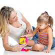 Child girl and mother playing together with puzzle toy — Stock Photo #14743393