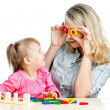 Mother and her child fun games with colorful toy — Stock Photo #14743415