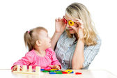 Mother and her child fun games with colorful toy — Stock Photo