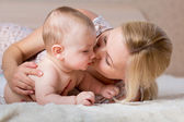 Loving mother kissing her baby — Stock Photo