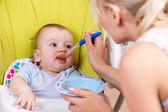 Mother spoon feeding her baby boy — Stock Photo