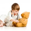 Adorable child with clothes of doctor and teddy bear over white — Stock Photo