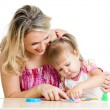 Stock Photo: Happy little kid and mother sitting at table and playing with co