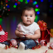 Baby girl with gifts under Christmas tree — Stock Photo