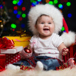 Baby girl in Santa Claus hat with gifts under Christmas tree — Stock Photo
