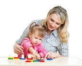 Moeder en haar kind spelen met kleurrijke puzzel speelgoed — Stockfoto