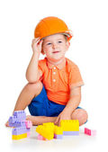 Cheerful child boy with hard hat playing with building blocks to — Stock Photo