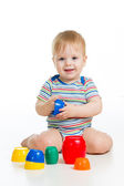 Funny little child is playing with toys while sitting on floor, — Photo
