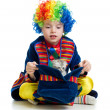 Boy clown with kitten inside hat over the white background - Stock Photo