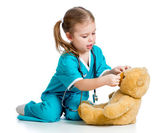 Doctor girl playing and curing toy isolated on white background — Photo