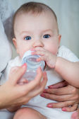 Mother feeding by milk his baby infant from bottle — Stock Photo