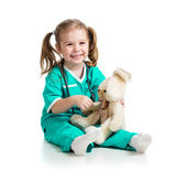 Adorable girl with clothes of doctor spoon playing with toy over — Stock Photo
