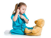 Adorable child with clothes of doctor examining teddy bear toy o — Stock Photo